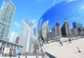 Les gratte-ciel se reflètent dans les panneaux d'acier de The Cloud Gate, surnommé le haricot.