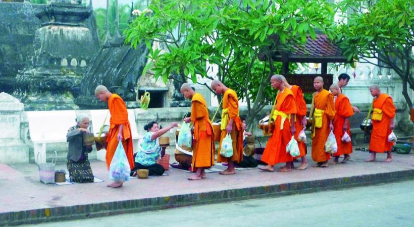 Au petit matin, les offrandes des fidèles  aux moines dans la rue principale.