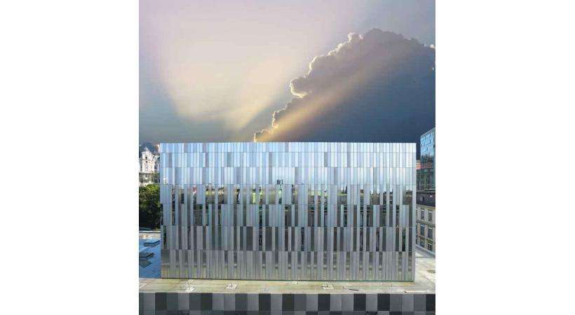 La façade sud du bâtiment composée d'une mosaïque de plaques de verre et d'inox.